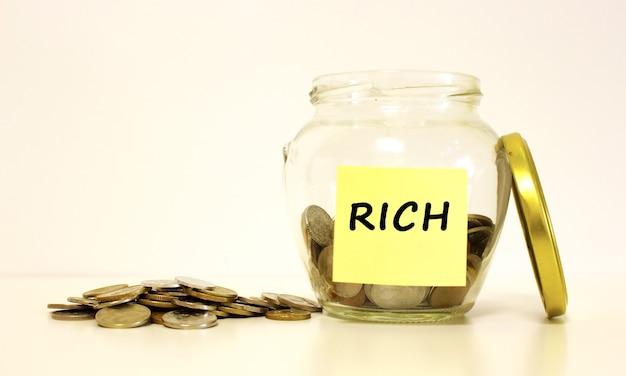 Szklany słoik z monetami na oszczędności. napis rich na papierze firmowym. koncepcja finansowa.