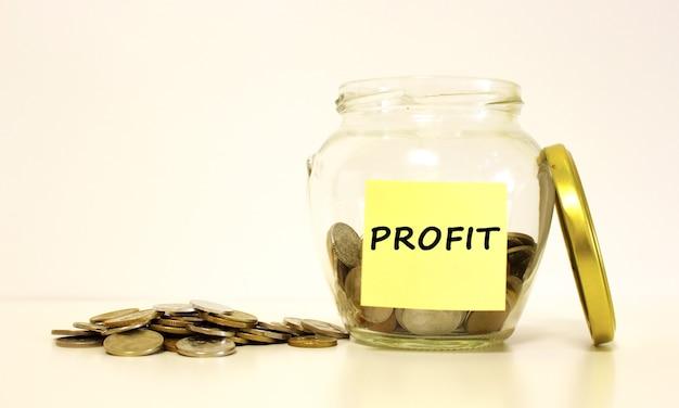 Szklany słoik z monetami na oszczędności. napis zysk na papierze firmowym. koncepcja finansowa.