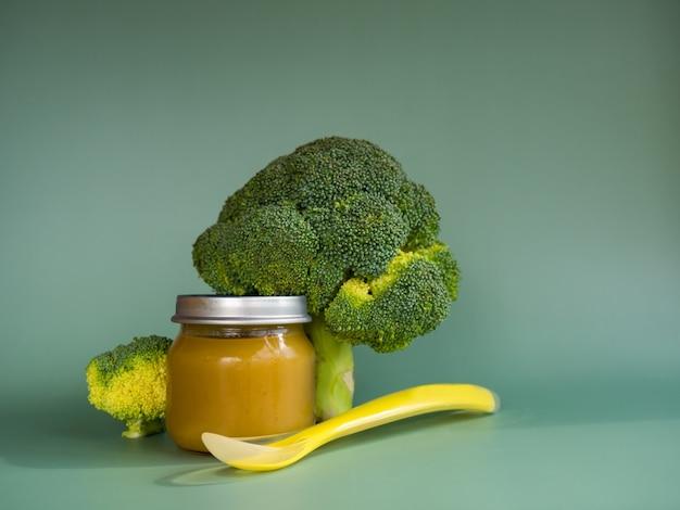 Szklany słoik z naturalnym jedzeniem dla dzieci na zielonym tle puree warzywne z selektywnym skupieniem brokułów