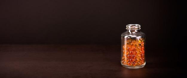 Szklany słoik z pigułkami o jaskrawym pomarańczowo żółtym kolorze na brązowym tle.