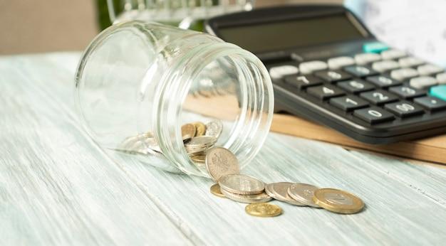 Szklany słoik z porozrzucanymi monetami i kalkulatorem na drewnianym stole.