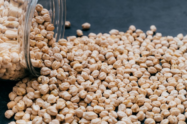 Szklany słoik z surowym garbanzo. ziarna ciecierzycy na białym tle na ciemnym tle. z bliska strzał. nasiona białek zdrowe jedzenie. składnik wegański