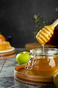 Szklany słoik ze świeżym miodem łyżka z jabłkiem i granatem koncepcja żydowskiego nowego roku szczęśliwe wakacje