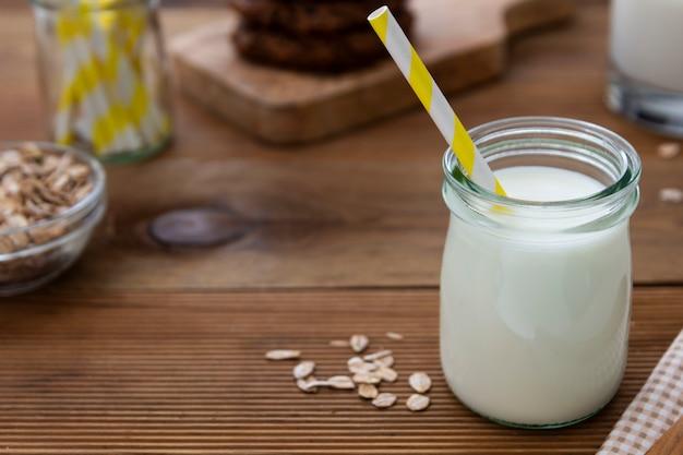 Szklany słój, butelka owsa mleko z papierową słomą na drewnianym tle