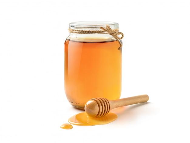 Szklany słój czysty miód z miodową chochlą odizolowywającą na białym tle.