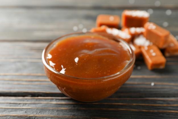 Szklany słój z sosem karmelowym i cukierkami na drewnianej przestrzeni, kopii przestrzeń
