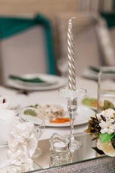 Szklany świecznik ze srebrną świecą i innymi dekoracjami znajduje się na biurku