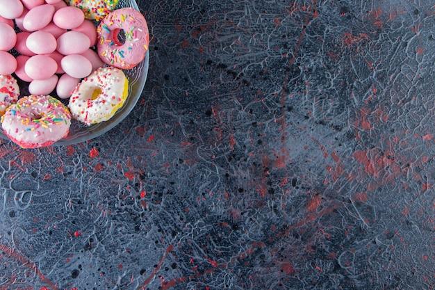 Szklany talerz kolorowych pysznych pączków i różowe cukierki na ciemnej powierzchni.