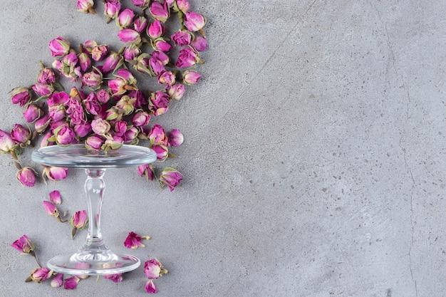 Szklany talerz pełen suszonych pąków kwiatowych róż umieszczony na kamiennym tle.