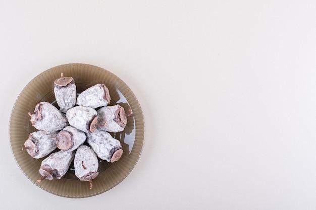 Szklany talerz pełen suszonych persimmons na białym tle. zdjęcie wysokiej jakości