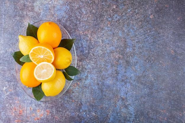 Szklany talerz pełen świeżych cytryn z liśćmi na marmurze.