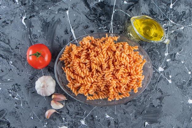 Szklany talerz pysznego makaronu fusilli i warzyw na marmurowej powierzchni.