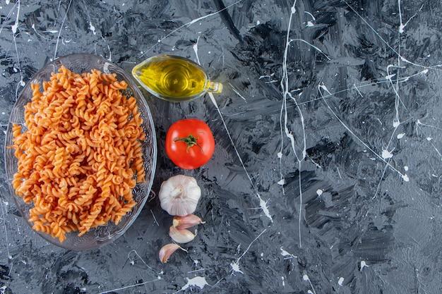 Szklany talerz pysznego makaronu fusilli i warzyw na tle marmuru.