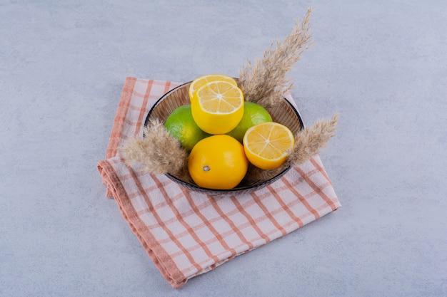Szklany talerz świeżych soczystych cytryn na kamieniu.
