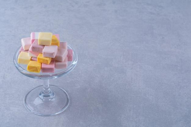 Szklany talerz z różowym i żółtym słodkim cukierkiem pastila.