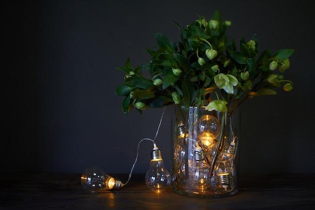 Szklany wazon wypełniony świecącymi żarówkami i bukietem ciemiernika