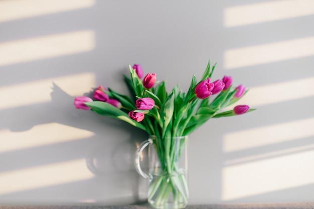 Szklany wazon z bukietem pięknych tulipanów na szarej ścianie