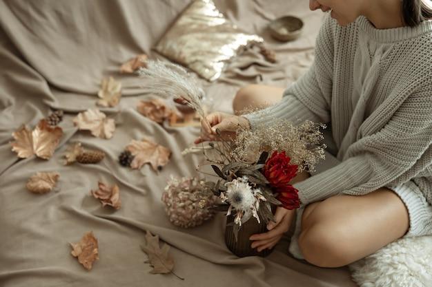 Szklany wazon z jesiennymi kwiatami w kobiecych rękach na niewyraźnym tle z jesiennymi liśćmi.