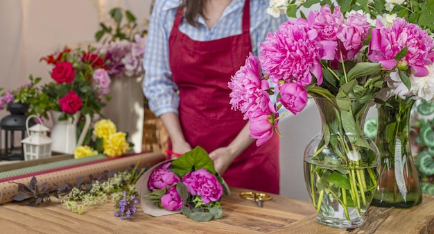 Szklany wazon z kwitnącymi piwoniami, saler kwiatów. biznes florystyczny. układ bukietów.
