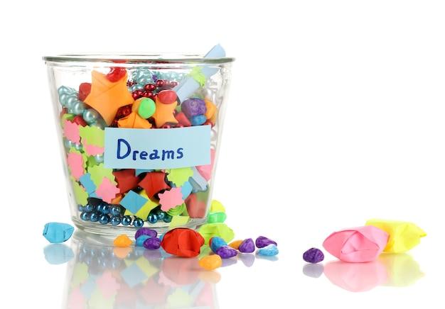 Szklany wazon z papierowymi gwiazdami z marzeniami na białym tle
