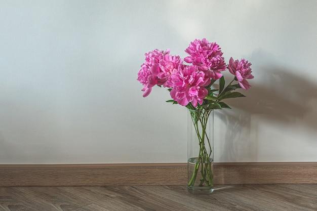 Szklany wazon z różowymi piwoniami na drewnianej podłodze