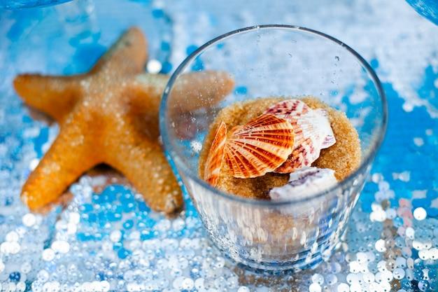 Szklany wazon ze słodkim piaskiem z brązowego cukru i różnymi muszlami