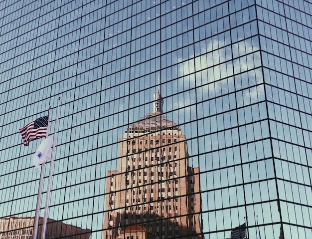 Szklany wieżowiec z amerykańską flagą i wysokim odbiciem budynku