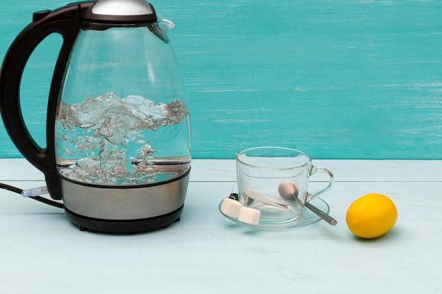 Szklany wrzący elektryczny czajnik na drewnianym stole.