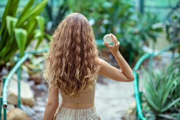 Szklarnia. długowłosa kobieta z kostką sopa w dłoniach