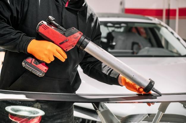 Szklarz nakładający gumowe uszczelnienie na przednią szybę w garażu, z bliska.