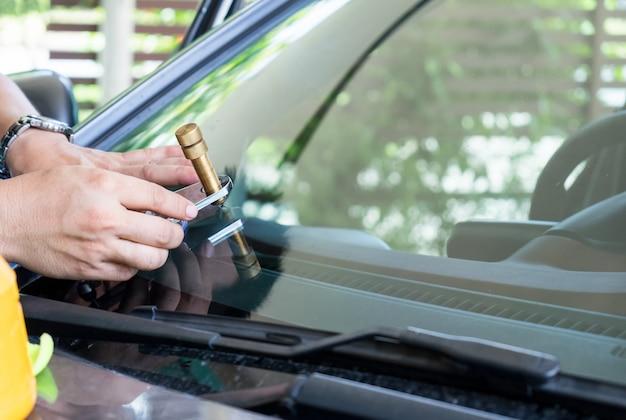 Szklarz używający narzędzi do naprawy pęknięć przedniej szyby