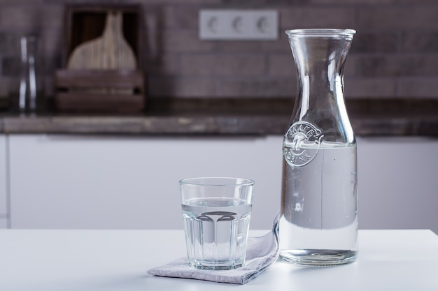 Szkło czysta woda i butelka na kuchennym stole. clean concept
