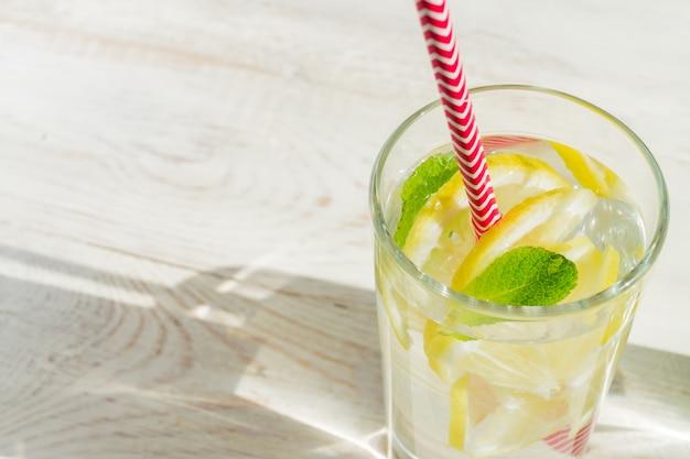 Szkło domowej lemoniady z cytryn, mięty i papierowych słomek na drewnianym nieociosanym tle. letni orzeźwiający napój.