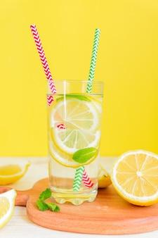 Szkło domowej roboty lemoniada z cytrynami, mennicą i zielonymi i czerwonymi papierowymi słoma na żółtym tle. letni orzeźwiający napój.