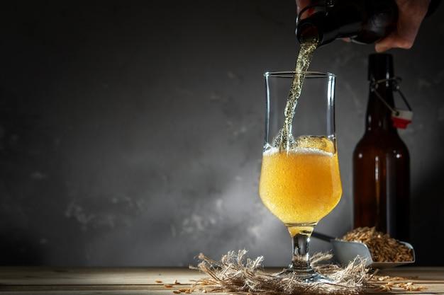 Szkło domowej roboty piwo na drewnianym stole. szklanka piwa rzemieślniczego na ciemnym tle.
