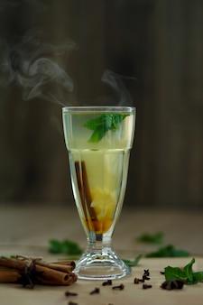 Szkło gorąca witaminy herbata na drewnianym stole. zimowe gorące napoje sezonowe