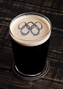 Szkło gruby piwo wierzchołek z olimpiadami kształtuje na drewnianym tle