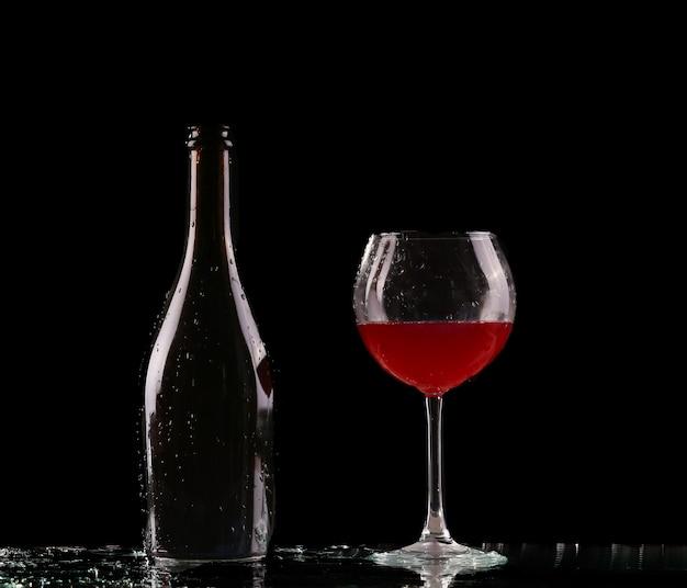 Szkło i butelka czerwonego wina plusk na czerni