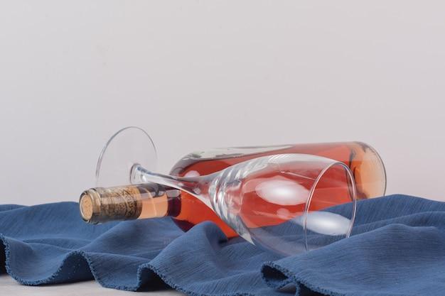 Szkło i butelka różowego wina na niebieskim obrusie.