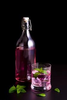 Szkło i butelka z fioletowym napojem