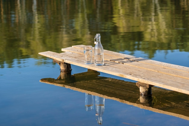 Szkło i butelka z wodą pitną na drewnianym molo rano w pobliżu jeziora i lasu w okresie wiosennym, z bliska. koncepcja przyrody i podróży