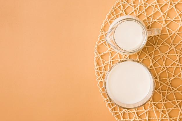 Szkło i dzbanek mleka na podkładce na kolorowym tle