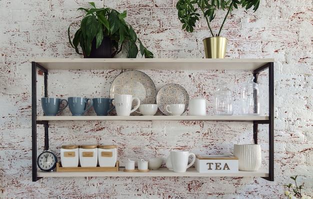 Szkło kuchenne kubki i tace na drewnianych i metalowych półkach kuchennych na ścianie