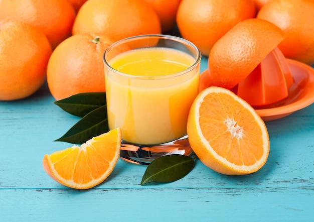 Szkło organicznie świeży pomarańczowy smoothie sok z surowymi pomarańczami na błękitnym drewnianym tle.