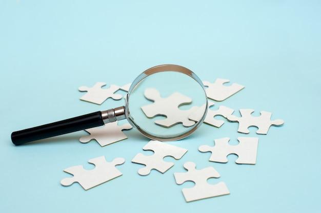 Szkło powiększające i białe puzzle na niebieskim tle