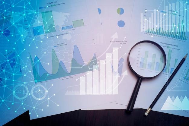 Szkło powiększające i dokumenty z danymi analitycznymi leżącymi na stole