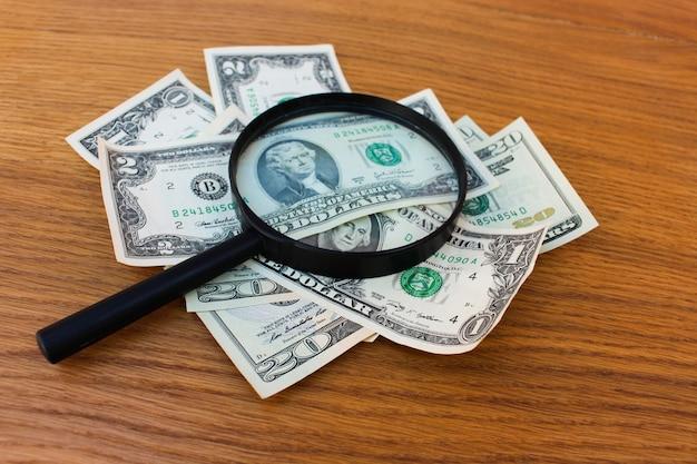 Szkło powiększające i dolary na stole