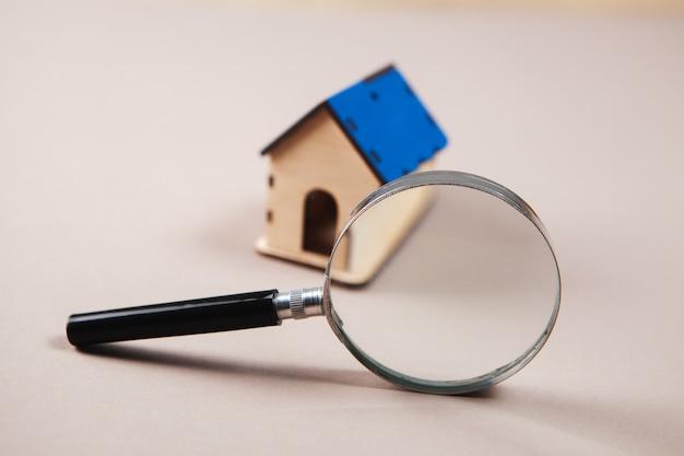 Szkło powiększające i dom na stole. koncepcja wyszukiwania domu.