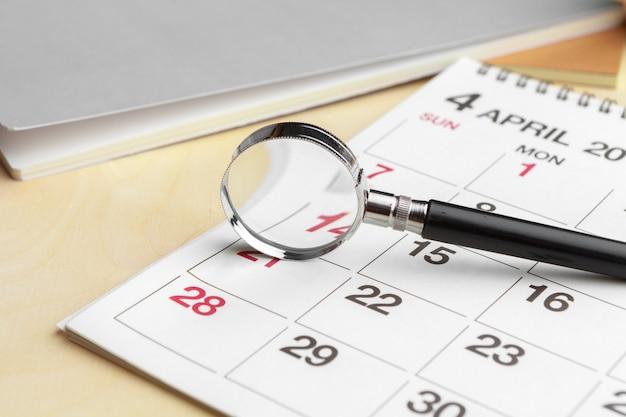 Szkło powiększające i kalendarz, koncepcja w biznesie i na spotkaniach