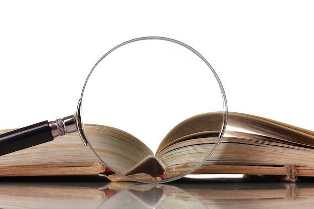 Szkło powiększające i książka na białym tle